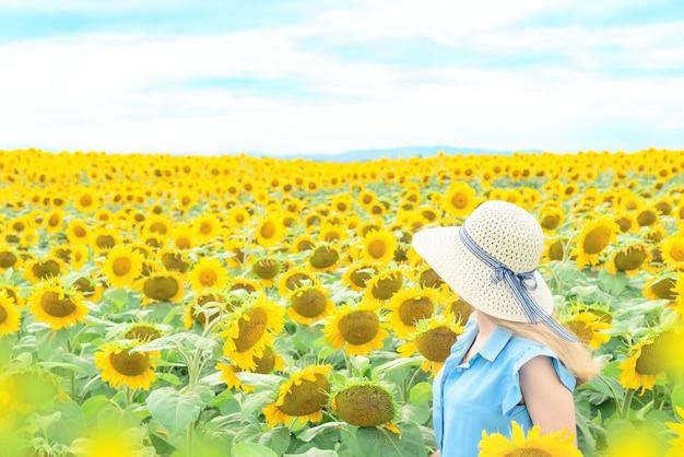 Jonge vrouw met een hoed in een veld met zonnebloemen