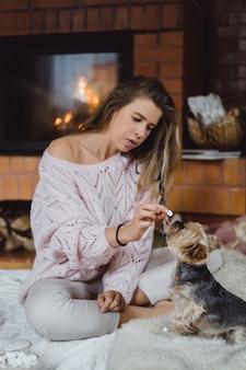 Jonge vrouw met een hond in de buurt van de open haard, drinkt cacao met marshmallows.