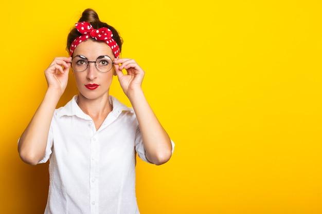 Jonge vrouw met een hoofdband zet haar bril recht op een gele muur. banner.