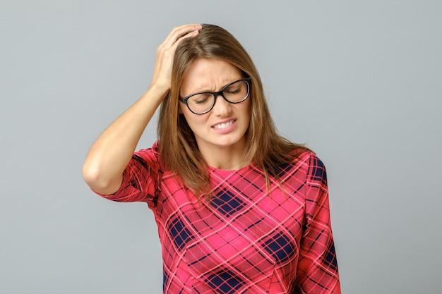 Jonge vrouw met een hoofdpijn aanraken van het hoofd