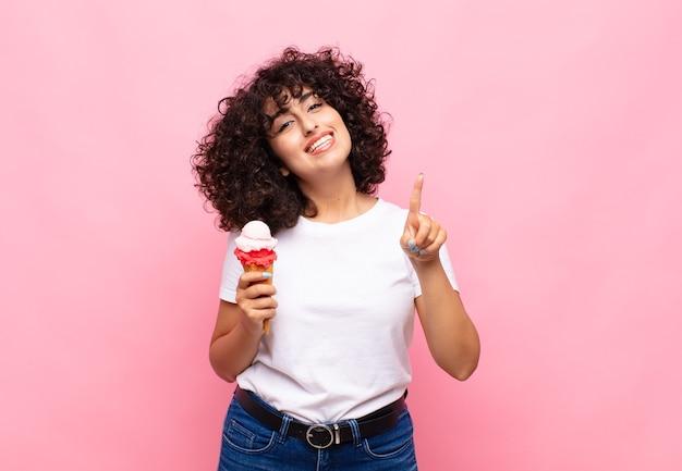 Jonge vrouw met een ijsje dat vriendelijk glimlacht en kijkt, nummer één toont of eerst met vooruit hand, aftellend