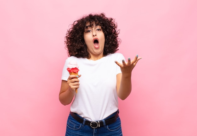 Jonge vrouw met een ijsje voelt zich extreem geschokt en verrast, angstig en in paniek, met een gestreste en geschokte blik