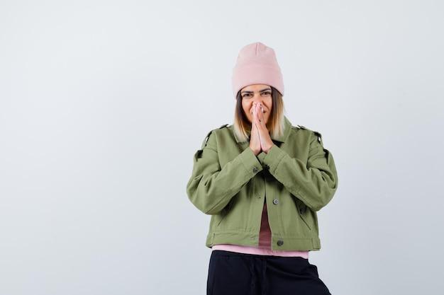 Jonge vrouw met een jas en een roze hoed in gebed