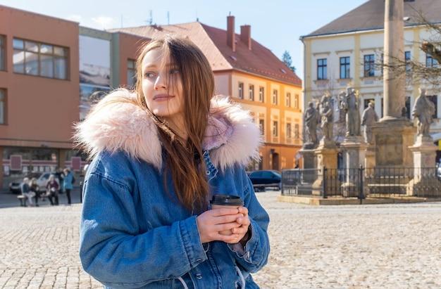 Jonge vrouw met een jas op straat met een kopje koffie
