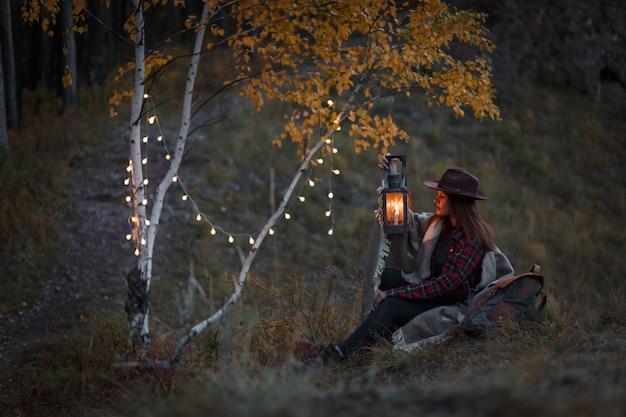Jonge vrouw met een kerosinelamp in het bos