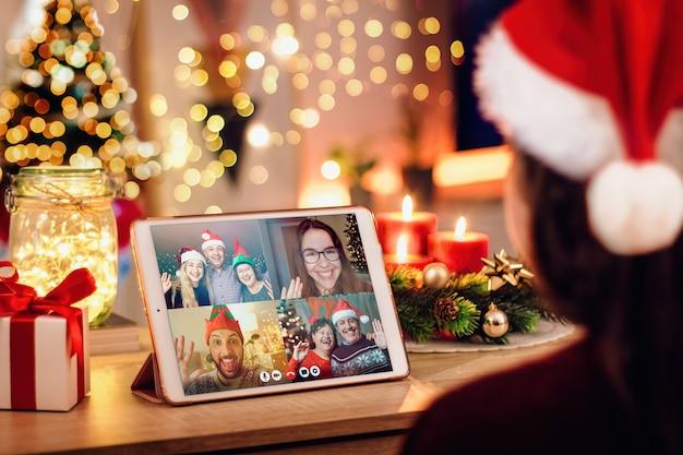 Jonge vrouw met een kerstvideogesprek met haar gelukkige familie. concept van gezinnen in quarantaine vanwege het coronavirus Premium Foto