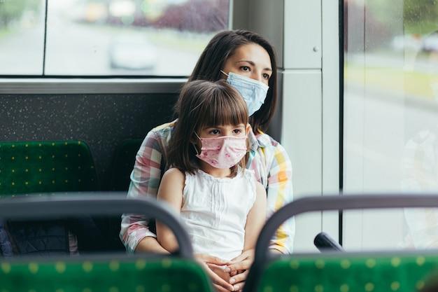 Jonge vrouw met een kind in een openbare bus beschermd met een beschermend masker op haar gezicht