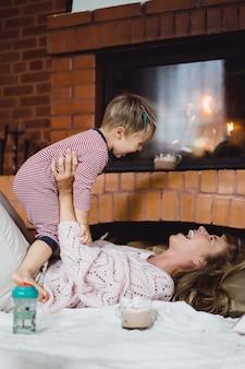 Jonge vrouw met een kind. moeder en zoon zijn aan het plassen, plezier maken bij de open haard.