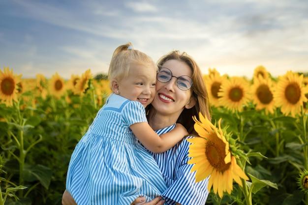 Jonge vrouw met een klein meisje in haar armen op een zonnebloem veld.