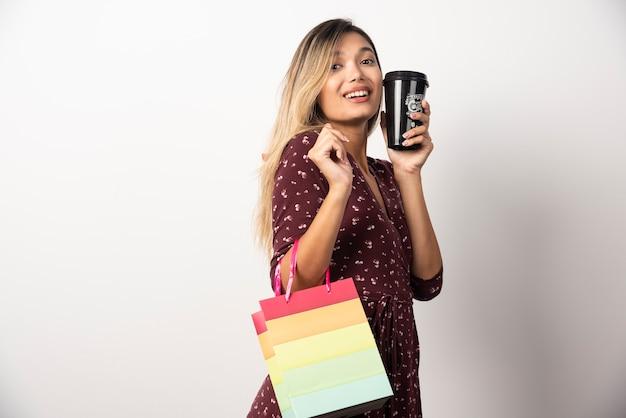 Jonge vrouw met een kleine winkeltas en een kopje drank op witte muur.