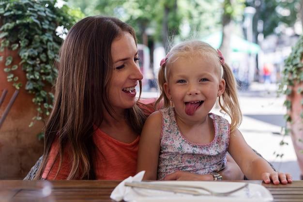 Jonge vrouw met een kleiner blond meisje dat wacht op een bestelling in een cafetaria.