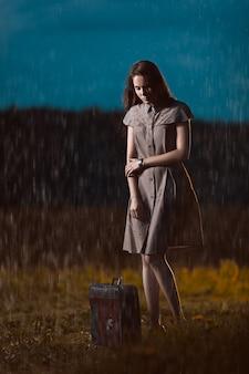 Jonge vrouw met een koffer die zich onder regen bevindt en wacht