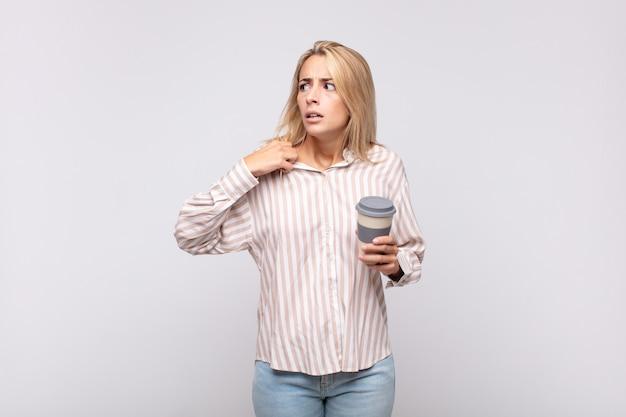 Jonge vrouw met een koffiegevoel dat gestrest, angstig, moe en gefrustreerd is, aan de hals van het shirt trekt, gefrustreerd kijkt door het probleem