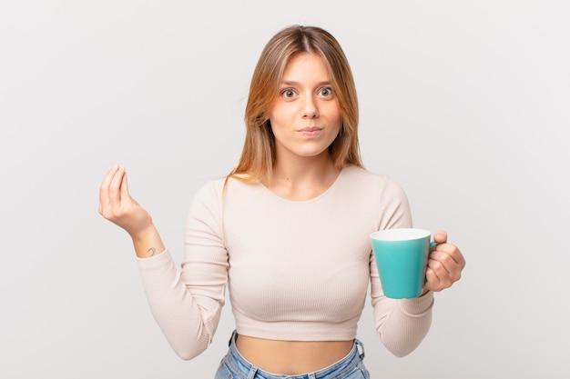 Jonge vrouw met een koffiemok die capice of geldgebaar maakt en zegt dat je moet betalen
