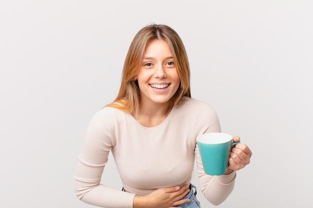 Jonge vrouw met een koffiemok die hardop lacht om een hilarische grap