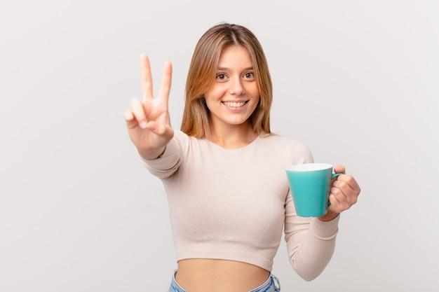 Jonge vrouw met een koffiemok die lacht en er gelukkig uitziet, gebarend naar overwinning of vrede