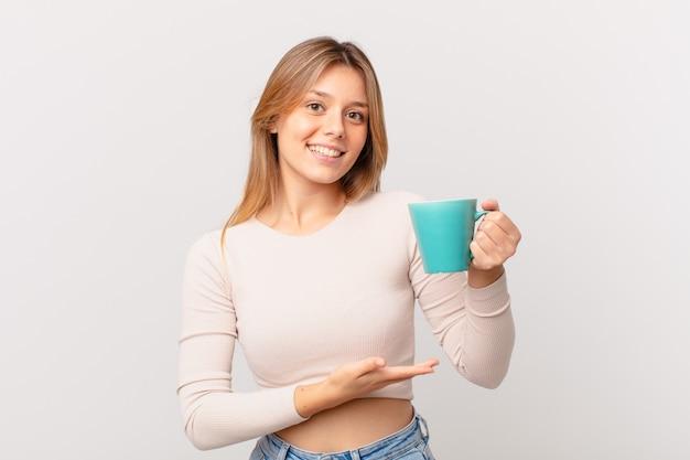 Jonge vrouw met een koffiemok die vrolijk lacht, zich gelukkig voelt en een concept toont