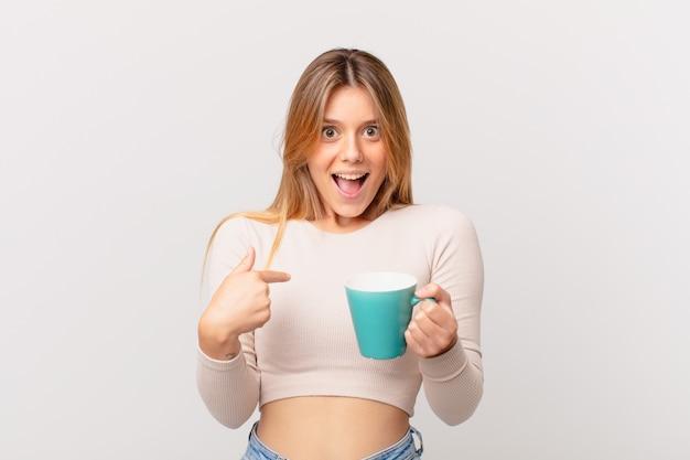 Jonge vrouw met een koffiemok die zich gelukkig voelt en naar zichzelf wijst met een opgewonden