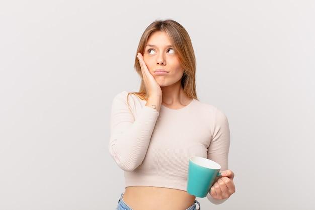 Jonge vrouw met een koffiemok die zich verveeld, gefrustreerd en slaperig voelt na een vermoeiende
