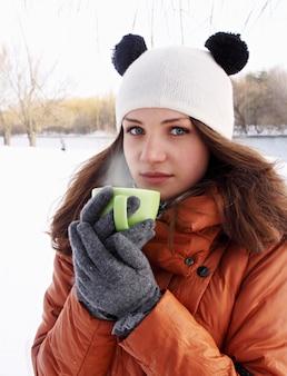 Jonge vrouw met een kop warme drank