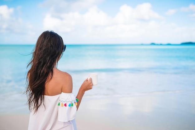 Jonge vrouw met een kop warme koffie geniet van vakantie