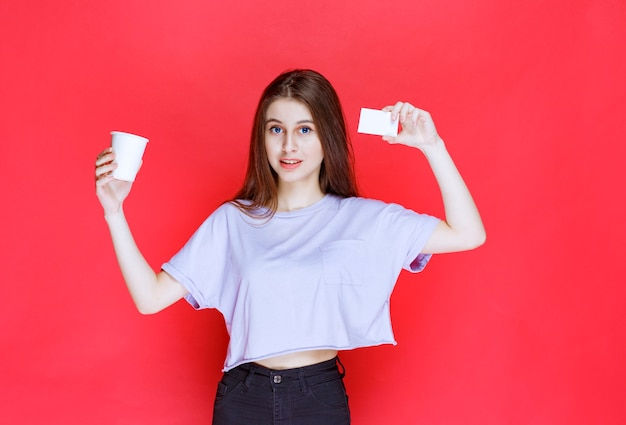 Jonge vrouw met een kopje drank haar visitekaartje presenteren.