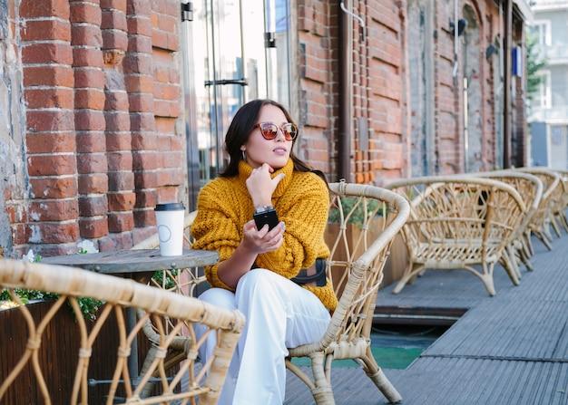 Jonge vrouw met een kopje koffie buitenshuis
