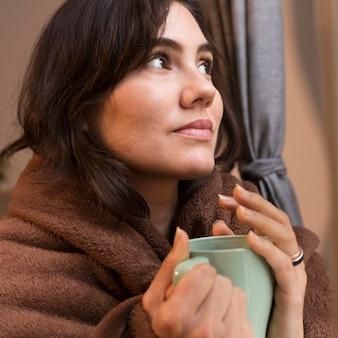 Jonge vrouw met een kopje koffie terwijl wordt bedekt met een deken Gratis Foto