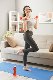 Jonge vrouw met een koptelefoon die traint met halter op yogamat op de voorbank in de woonkamer