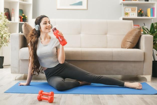 Jonge vrouw met een koptelefoon die traint op een yogamat met een waterfles voor de bank in de woonkamer