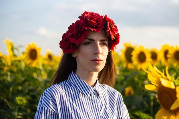 Jonge vrouw met een krans van rode bloemen kijkt naar de zonsondergang op een zonnebloemveld.