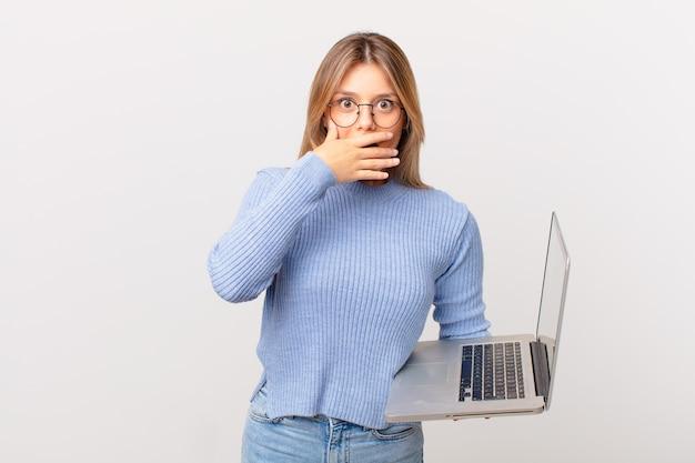 Jonge vrouw met een laptop die de mond bedekt met handen met een geschokt