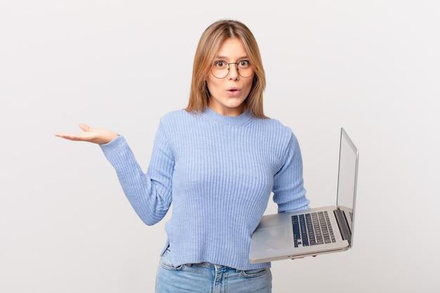 Jonge vrouw met een laptop die er verrast en geschokt uitziet, met open mond terwijl ze een voorwerp vasthoudt