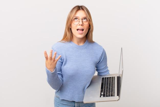 Jonge vrouw met een laptop die er wanhopig, gefrustreerd en gestrest uitziet