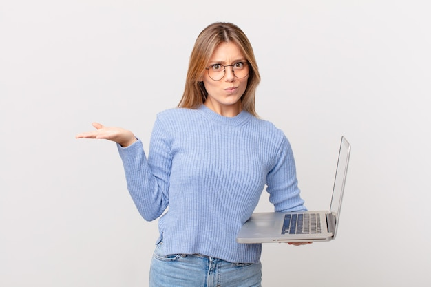 Jonge vrouw met een laptop die zich verward en verward en twijfelt