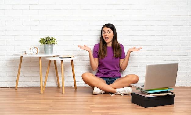 Jonge vrouw met een laptop zittend op de vloer bij binnen met geschokte gezichtsuitdrukking
