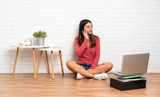 Jonge vrouw met een laptop zittend op de vloer binnenshuis houden een gesprek met de mobiele telefoon met iemand
