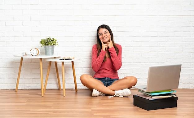Jonge vrouw met een laptop zittend op de vloer binnenshuis lachend met een gelukkige en aangename uitdrukking