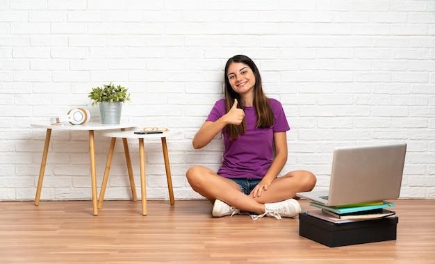 Jonge vrouw met een laptop zittend op de vloer binnenshuis met een duim omhoog gebaar