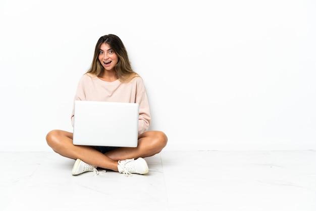 Jonge vrouw met een laptop zittend op de vloer geïsoleerd op een witte achtergrond met verrassingsgelaatsuitdrukking