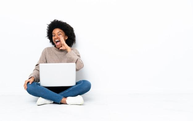 Jonge vrouw met een laptop zittend op de vloer schreeuwen met wijd open mond