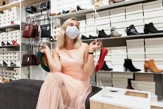 Jonge vrouw met een masker in een schoenenwinkel kiest een product. coronapandemie.