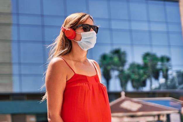 Jonge vrouw met een masker, luisteren naar muziek in de stad