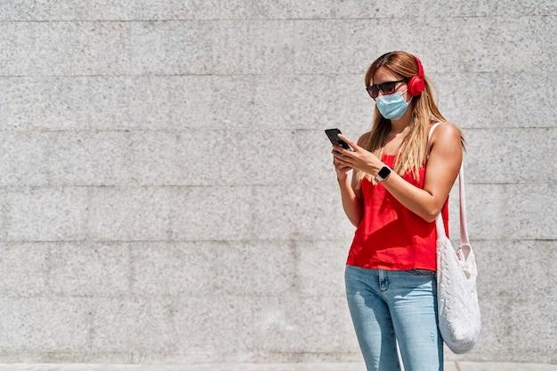 Jonge vrouw met een masker met haar mobiele telefoon in de stad