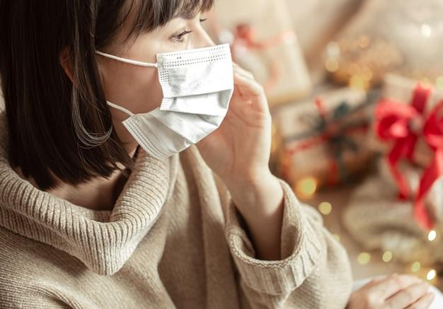Jonge vrouw met een masker op haar gezicht in een gezellige beige trui. het concept van kerst tijdens het coronavirus.