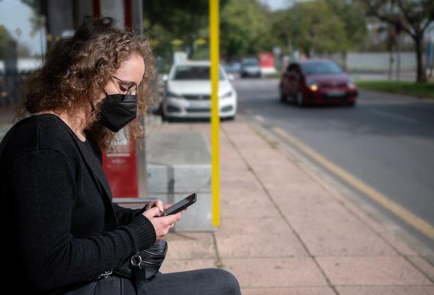 Jonge vrouw met een masker zit bij een bushalte te typen op haar smartphone