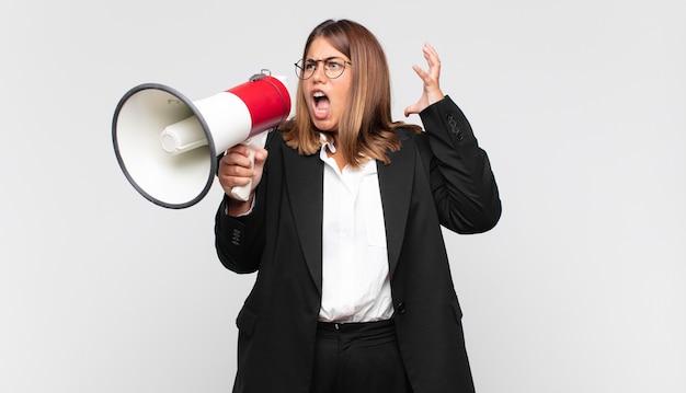 Jonge vrouw met een megafoon die met de handen in de lucht schreeuwt, zich woedend, gefrustreerd, gestrest en boos voelt