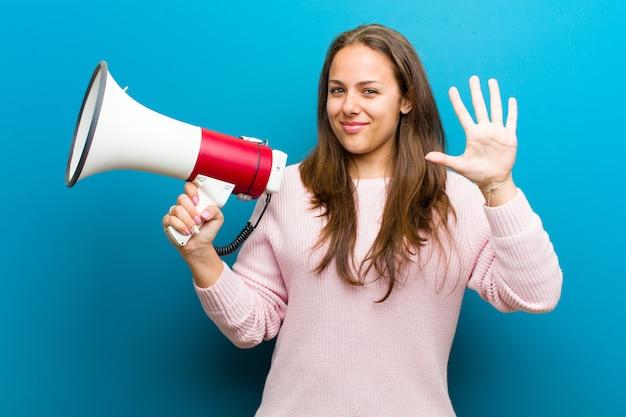 Jonge vrouw met een megafoon tegen de blauwe muur
