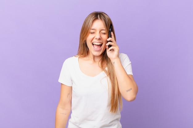 Jonge vrouw met een mobiele telefoon die agressief schreeuwt, erg boos kijkt