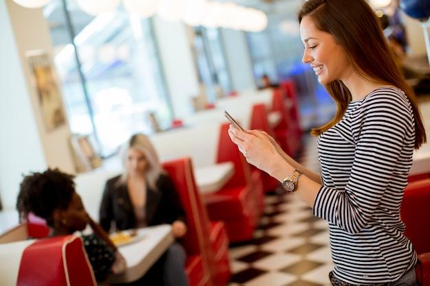 Jonge vrouw met een mobiele telefoon in het diner
